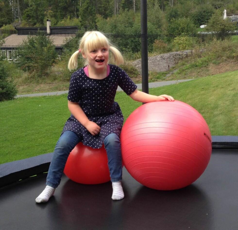GLADJENTE: Til tross for utfordringene er Anna ei aktiv jente som storkoser seg i trampolina. Foto: Privat