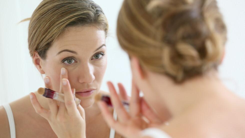 FJERN MØRKE RINGER: Som mange andre har du nok godt for en lys, hudfarget concealer for å fjerne mørke ringer og poser under øynene. Det er faktisk slik at oransje er fargen du bør gå for. Les hvorfor og få mange andre tips nede i saken! Foto: Shutterstock / Goodluz