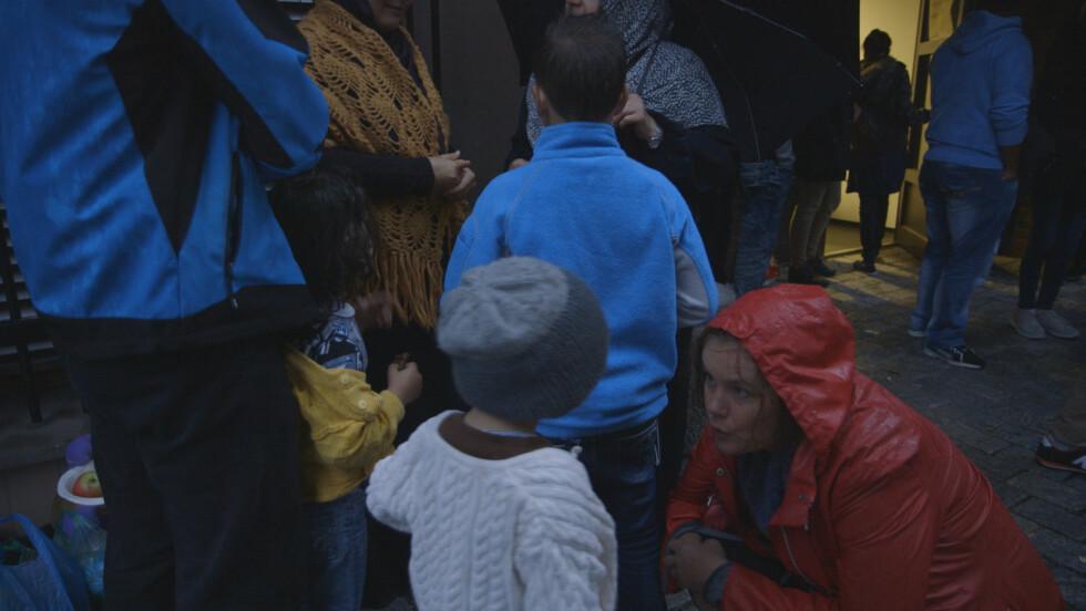 SAMTALER: Mona Bentzen i samtale med et nyankommet barn under middagsserveringen på Tøyen.  Foto: Line Lyngstadaas
