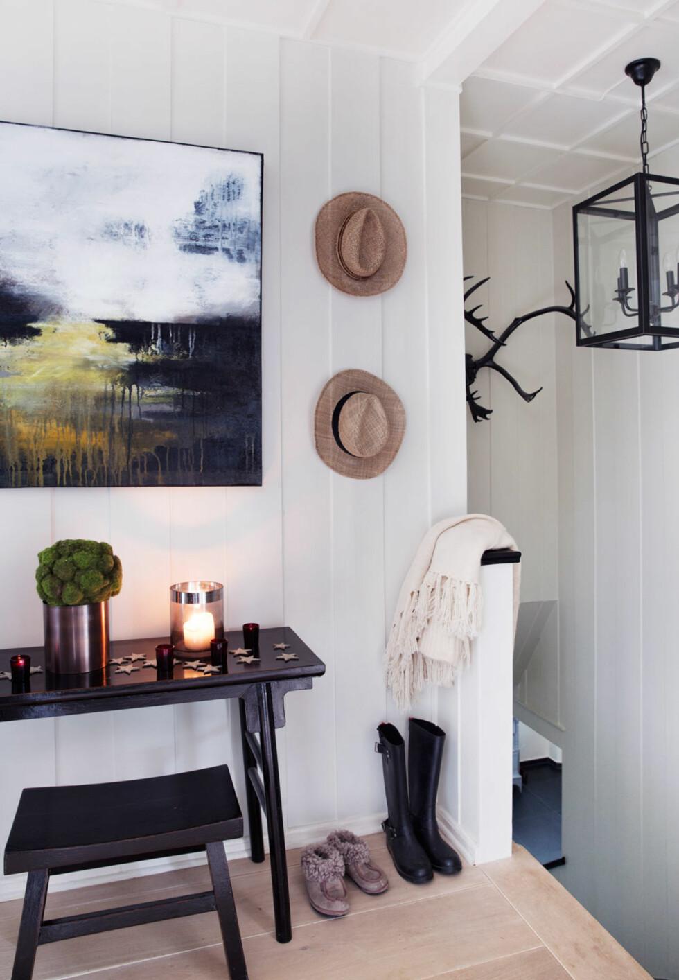 Bord, krakk og lampe fra Slettvoll. Små duftlys fra Ralph Lauren, hatter fra reiser i Italia og bilde malt av Cecilie. Geviret fra selvskutt rein.  Foto: Yvonne Wilhelmsen