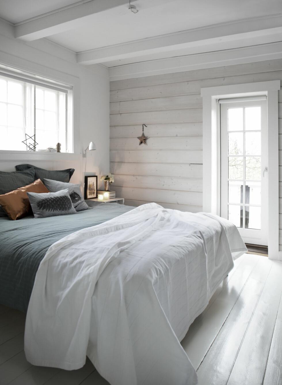MANGE PUTER PÅ SENGA: Det koselige soverommet er hvitt og stilrent, men de kule putene bryter med uttrykket.   Foto: Ina Agency