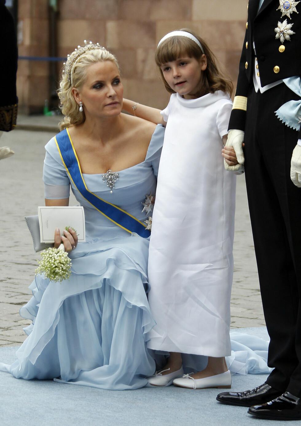 TRYGT: Prinsesse Ingrid Alexandra støttet seg til sin mor kronprinsesse Mette-Marit og far kronprins Haakon etter vielsen mellom kronprinsesse Victoria og prins Daniel i Storkyrkan i Stockholm i 2010. Inntrykkene var nok mange for den da seks år gamle prinsessen - som hadde fått det ærefulle oppdraget med å være brudepike. Foto: NTB Scanpix