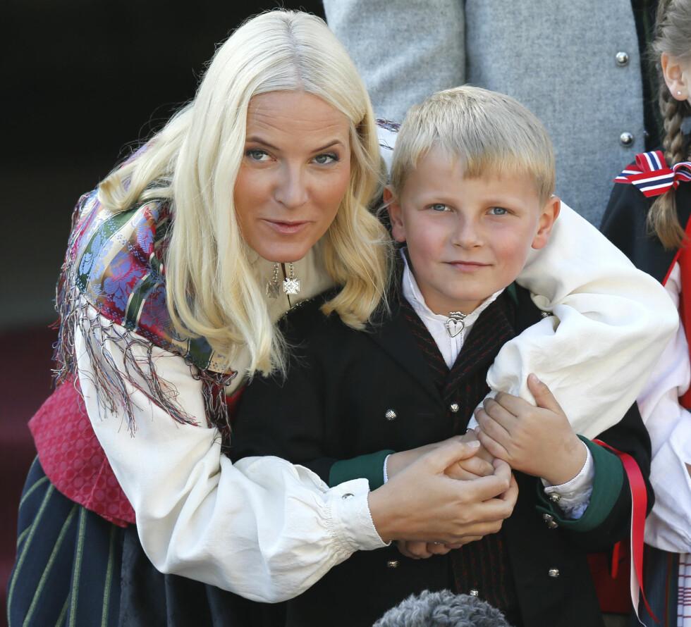 GO' PRINSEN: Også prins Sverre Magnus blir forberedt på den kommende representasjonsrollen. Her får han en god kos av mamma kronprinsesse Mette-Marit under barnetoget i Asker på 17. mai. Foto: NTB Scanpix