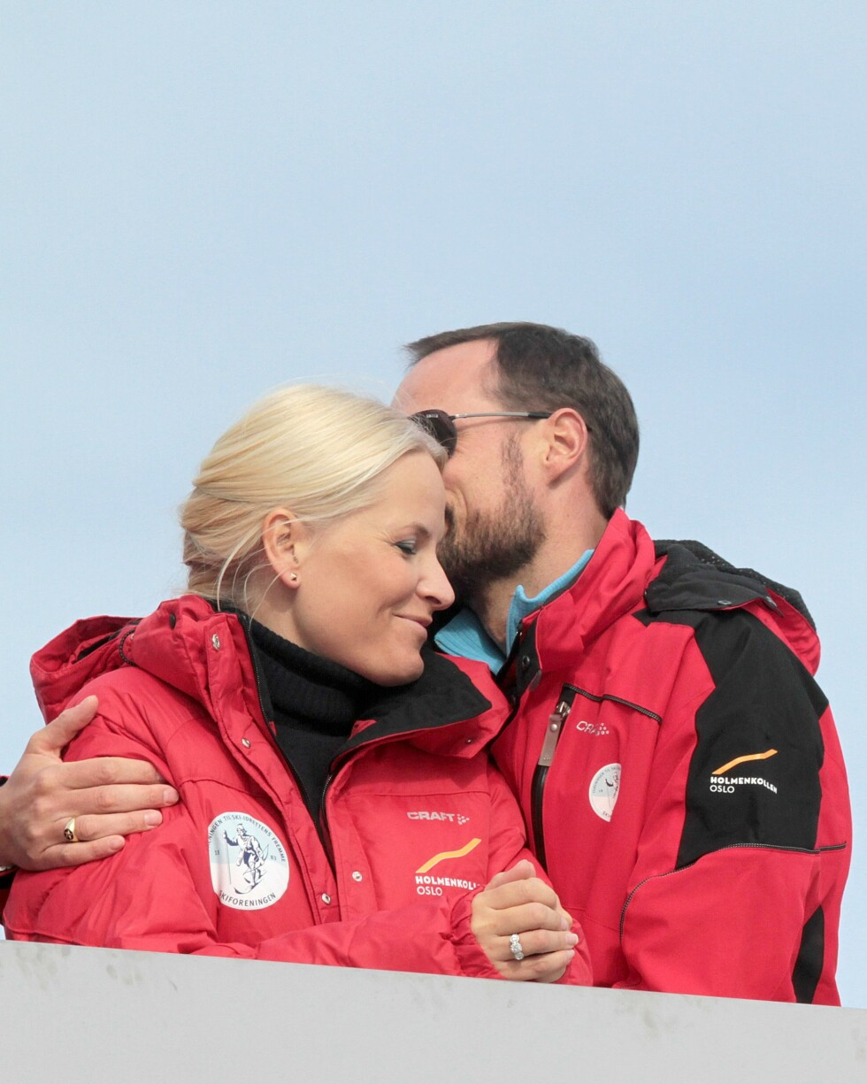 <strong>FORELSKET:</strong> Kronprins Haakon ga sin flotte kone Mette-Marit et kyss på kinnet under verdenscupen i hopp i Holmenkollen i mars 2012. De matchet i dunjakker fra Norges Skiforbund. Foto: NTB Scanpix