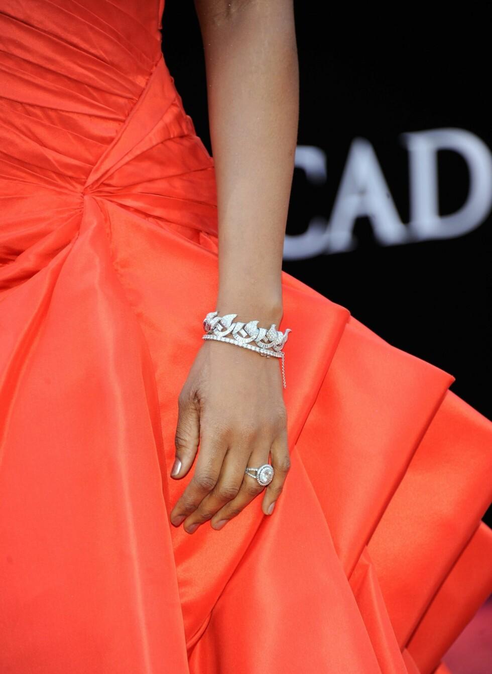 Skuespiller Jennifer Hudson i oransje kjole og bling bling rundt armen.   Foto: All Over Press