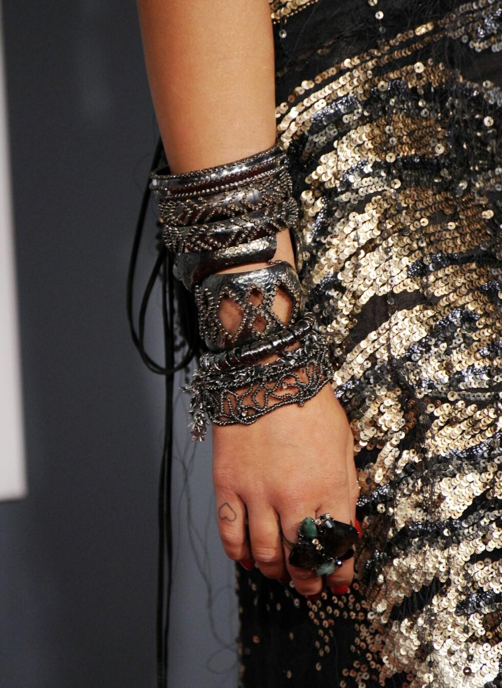 Popstjerne Miley Crrus med rocka armbånd til glitrende shiny paljettkjole.  Foto: All Over Press