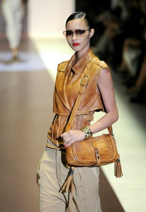 I GULL: Modell på catwalken til Gucci i safariinspirert 70-tallsantrekk stylet med lysebrun veske og gullarmbånd. Foto: All Over Press