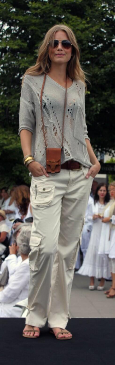 AVSLAPPET STIL: Modell i heklet strikkegenser med flettedetaljer, lysebrun iPhone-veske i skinn rundt halsen, løse beige bomullsbukser og lave sandaler. Foto: Cecilie Leganger