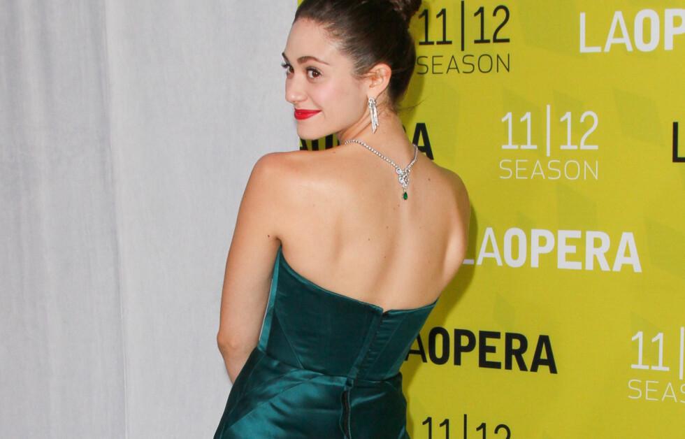 DEN LEKRE BAKSIDEN: Skuespiller Emmy Rossum vet å snu ryggen til fotografene for å vise fram både kjolen og smykket sitt. Stjel trikset og få det meste ut av neste sesongs aller største trend. Foto: All Over Press