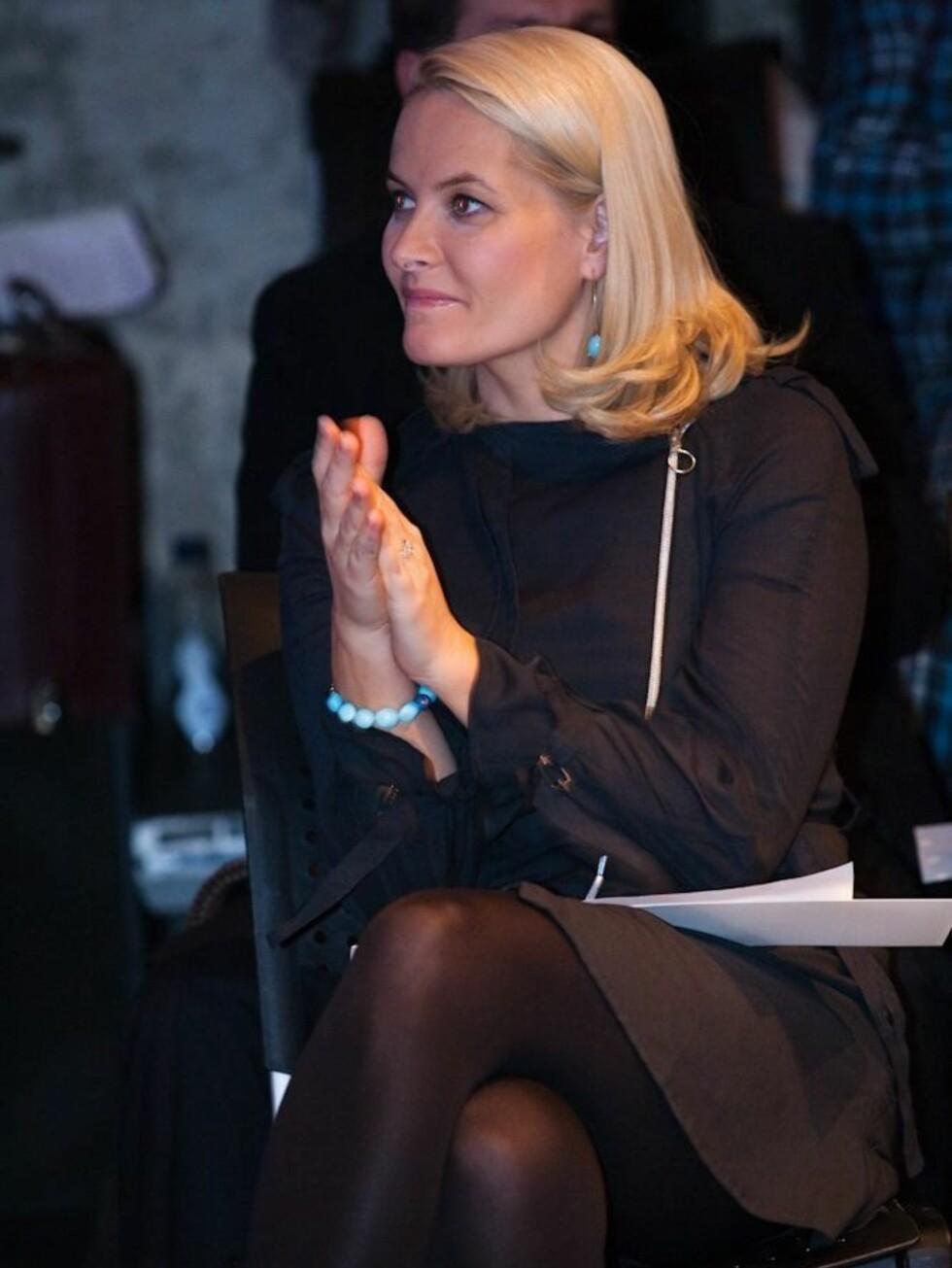 Kronprinsesse Mette-Marit valgte svarte, tykke strømpebukser som tilbehør til FIN-kjolen hun hadde på seg under moteuken, sammen med turkist armbånd og matchende ørepynt. Foto: Kjersti Staarvik