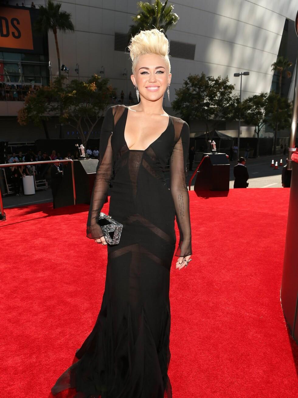 Popstjerne og skuespiller Miley Cyrus stilte i en svart kjole signert Emilio Pucci , Edie Parker clutch og smykker fra Lorraine Schwartz. Foto: All Over Press