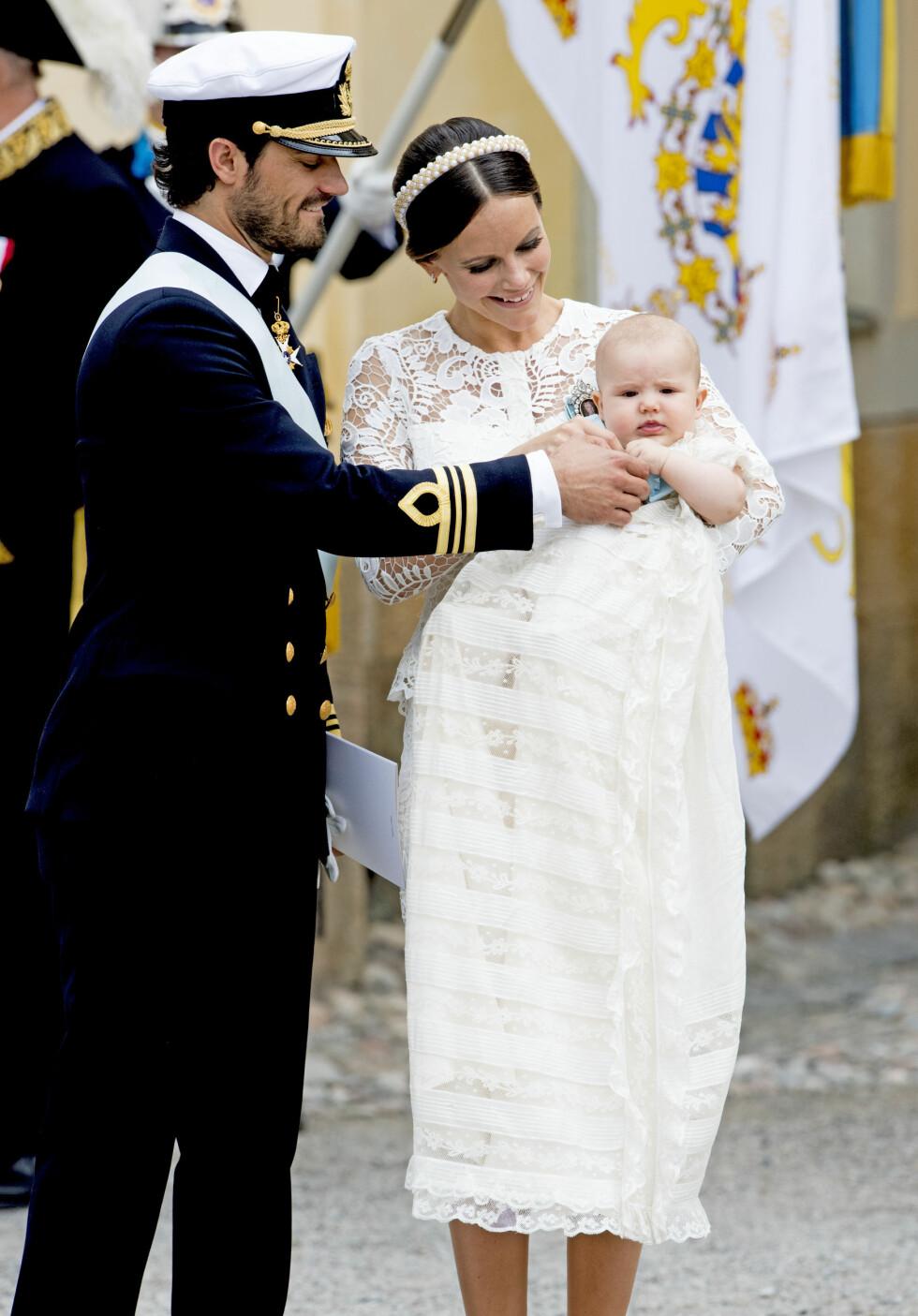 STOLTE FORELDRE: Prins Carl Philip og prinsesse Sofia viste fram dåpsbarnet til folket. Han var ikledd en dåpskjole som ble tatt i bruk for første gang i 1906.  Foto: NTB Scanpix