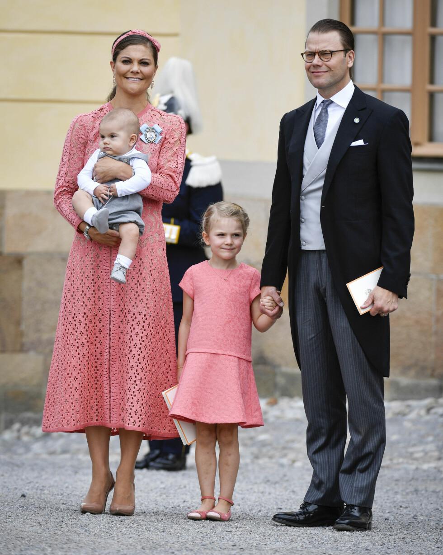 FIN FAMILIE: Kronprinsesse Victoria hadde prins Oscar på armen under hele dåpsseremonien, mens ektemannen prins Daniel passer på prinsesse Estelle. Se som mor og datter matcher i ferskenfargede kjoler. Foto: NTB Scanpix
