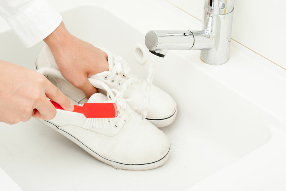 FOR HÅND: Prøv først å børste og tørke av skoene for å fjerne skitt og sand. Du kan også bruke litt vann på en klut for å ta skitt som sitter godt.  Foto: Shutterstock / beeboys