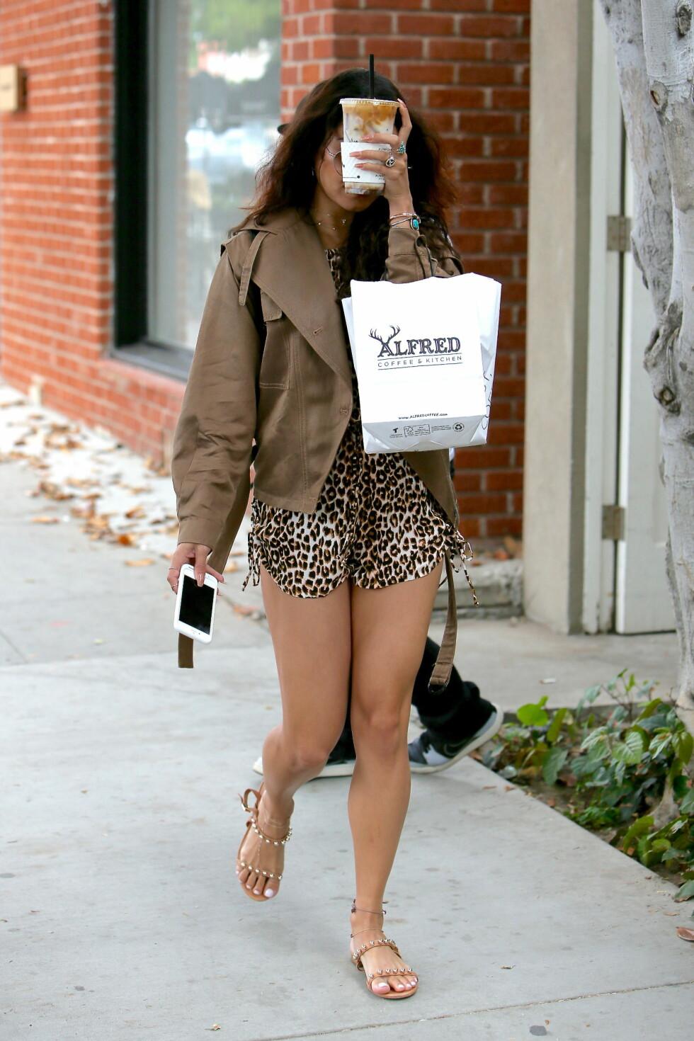 IKKE INTERESSERT: Vanessa Hugdens gjemmer nok en gang ansiktet sitt - denne dagen har hun byttet ut lommeboken med kaffen sin! Foto: wenn.com