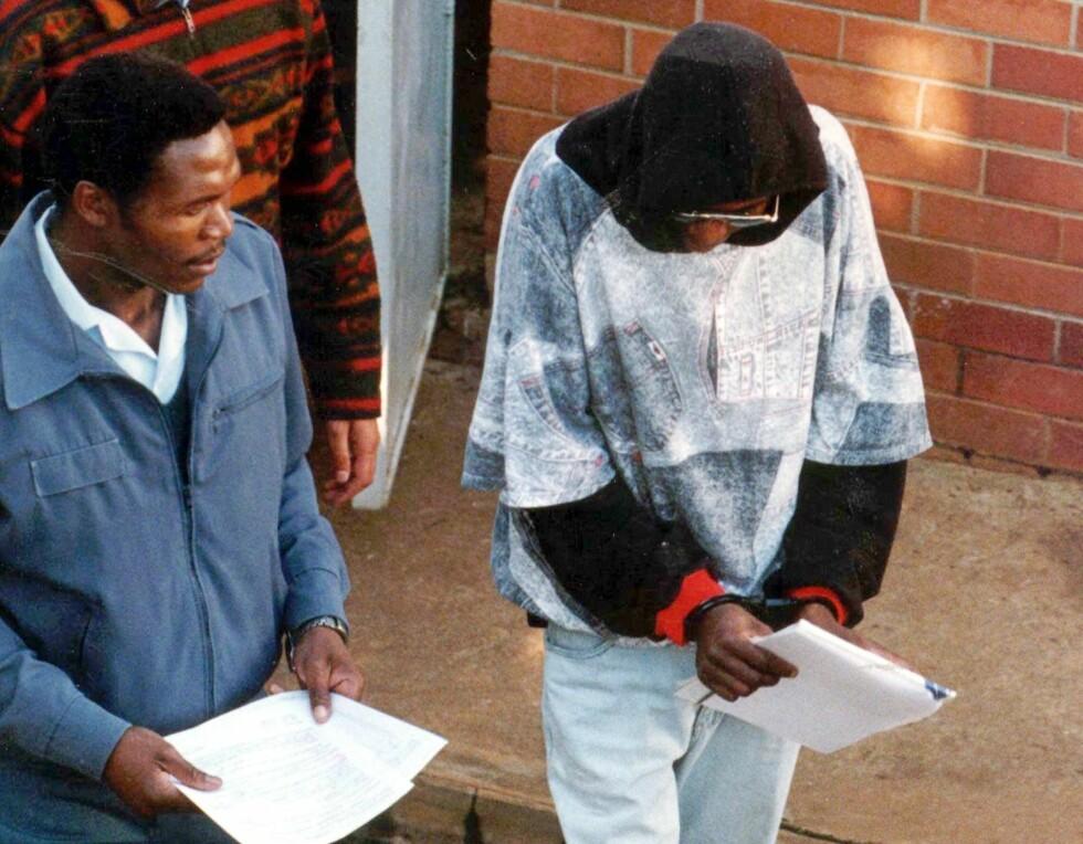 MOSES SITHOLE: Sithole (til høyre) blir ledet vekk fra retten året før han ble dømt til mer enn 2400 år i fengsel fredag 5.desember 1997.  Foto: AP