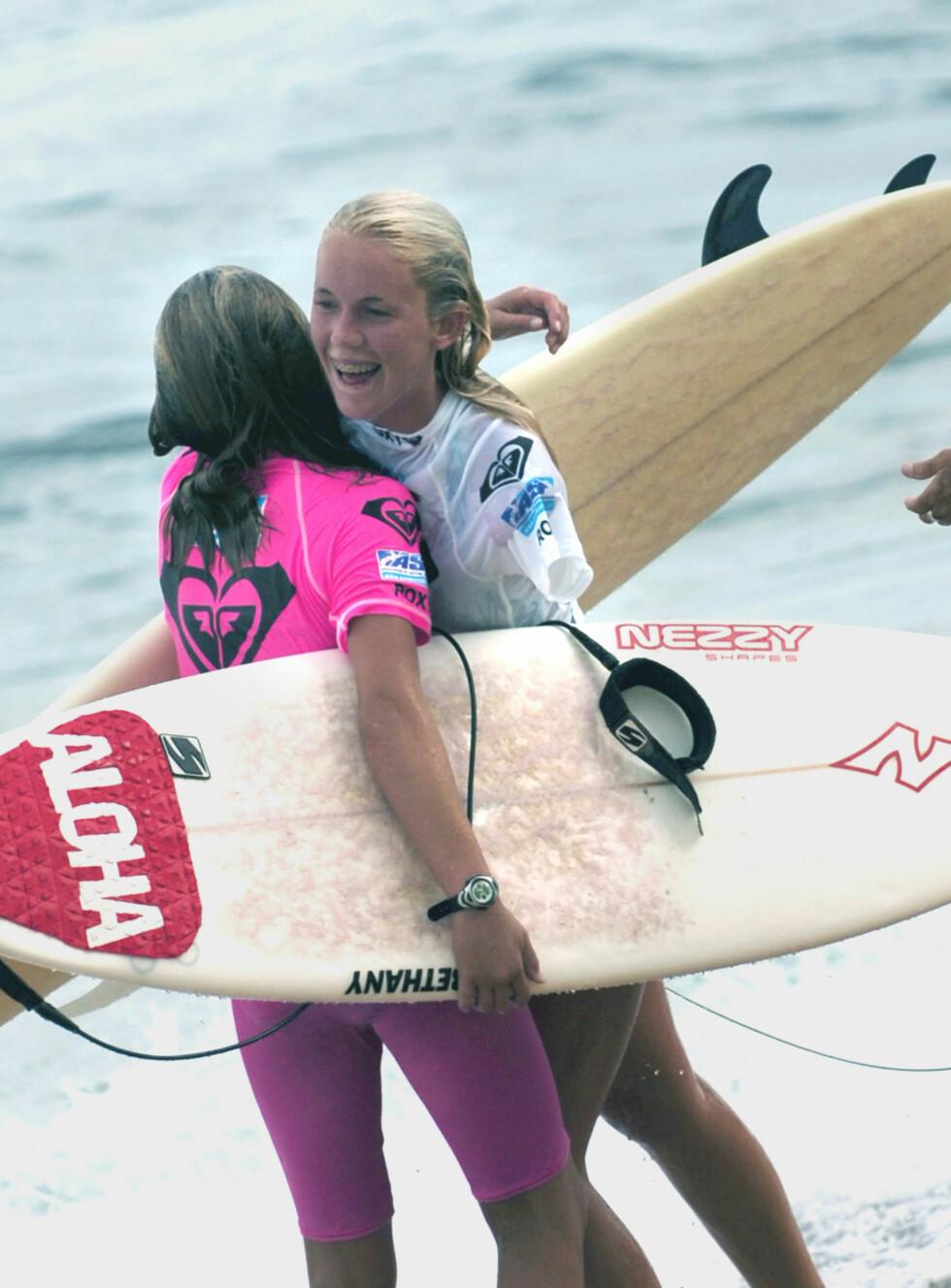 I MILJØET: Bethany Hamilton og surfervenninnen Carissa Moore ga hverandre en god klem etter en konkurranse på Hawaii to år etter ulykken. Foto: NTB Scanpix