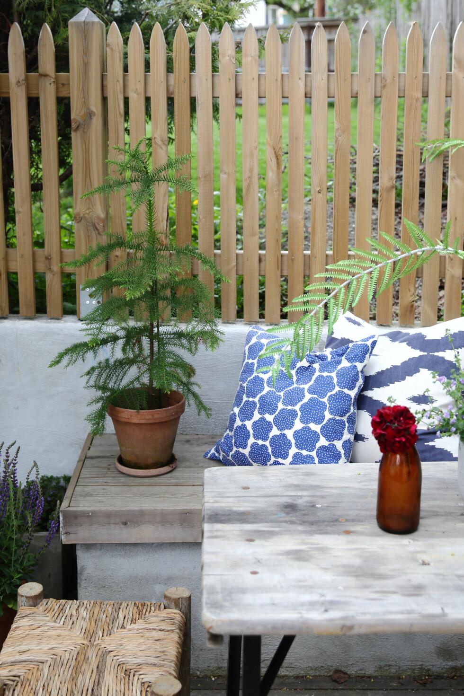 ALT I ETT: Bygg flerbruksmøbler som bare blir finere av å stå ute! Mur opp en enkel benk, og gi den et trelokk, så har du et møbel som kan brukes både til oppbevaring, som benk til potteplantene dine eller som et fint sted å sitte. Om du ikke er så superhandy selv, kan du sikkert få noen til å hjelpe deg med utførelsen så lenge du har ideen. Puter (kr270 og 390, Country Chic).  Foto: Krista Elvheim