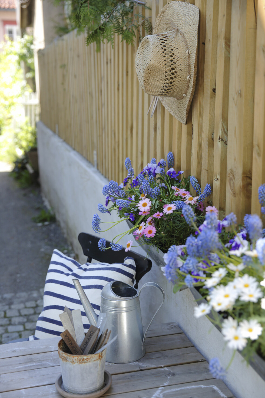 RAM DET INN: Du trenger ikke veranda for å bruke verandakasser, de kan like gjerne være med på å ramme inn en fin del av hagen ved åhenge dem på gjerdet. Gi spiseplassen en vakker og vilter «blomstervegg» med noen verandakasser ved bordenden.    Foto: Krista Elvheim