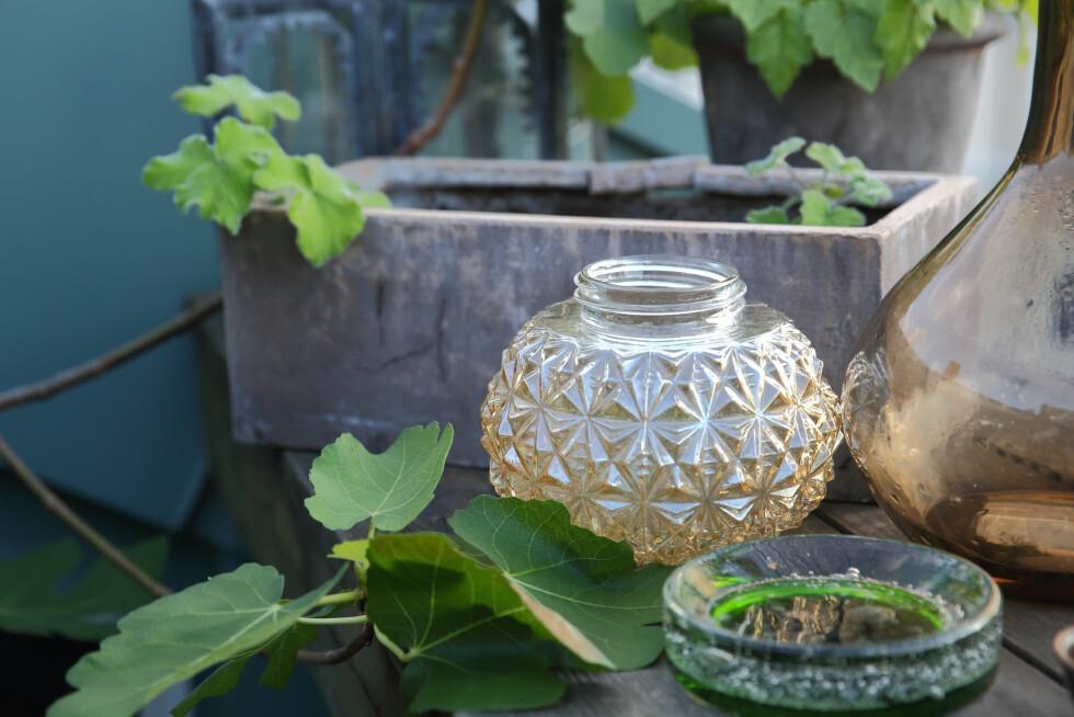 FIN GJENBRUK: Skap stemning med farget glass, og gjenbruk gamle lampekupler til telysene dine. De tykke, fargede glassproduktene som minner om 70-tallet, er tilbake for fullt, og de blir ekstra lekre når kveldsolen danser i lyset på sene sommerkvelder. Har du noen gamle lampekulper liggende, blir de til helt geniale lykter!  Foto: Krista Elvheim