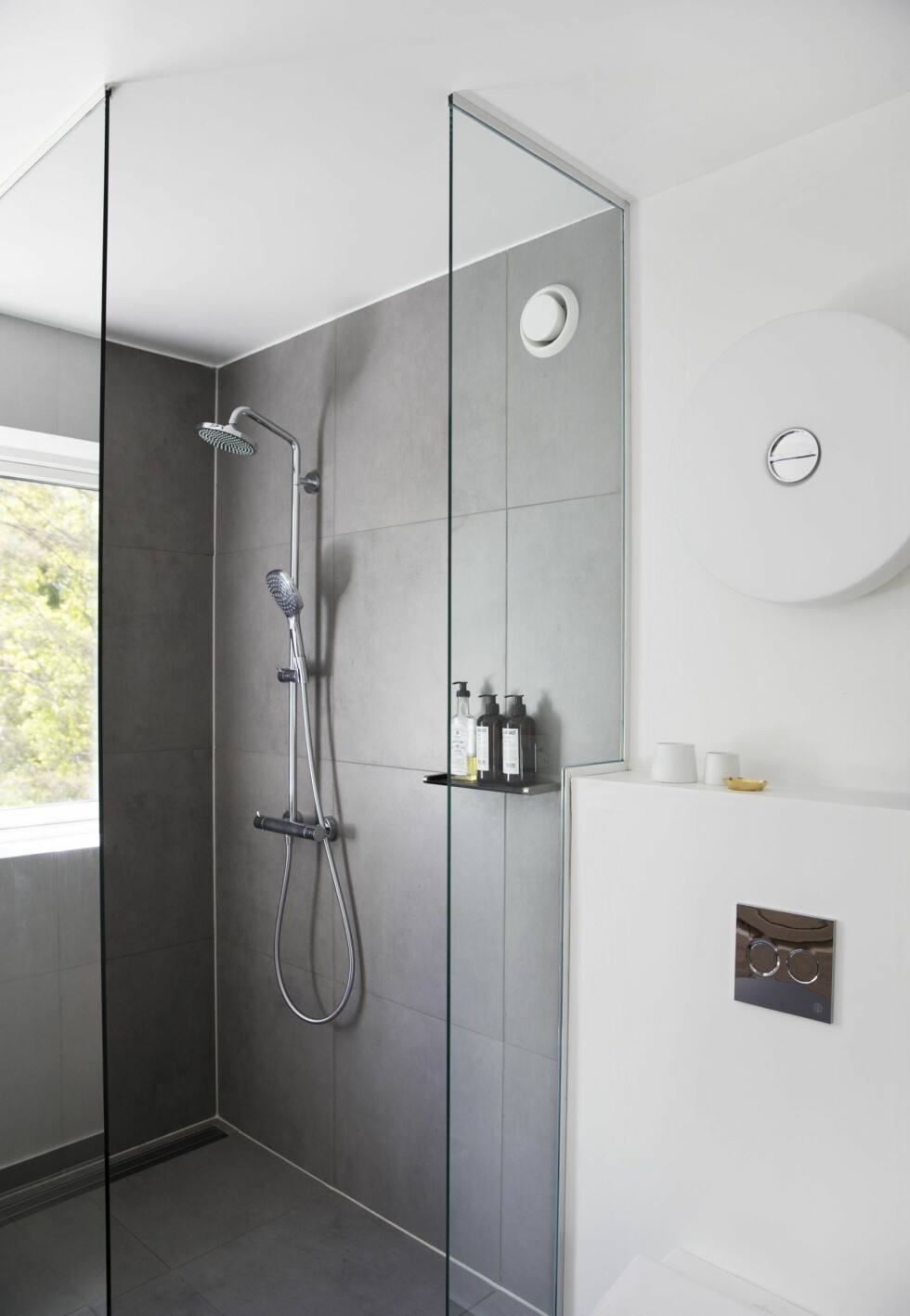 <strong>STORE FLISER:</strong> Badet er delikat innredet med fliser på både gulvet og i dusjnisgjen, 60 x 60 cm i fargen Sement fra Norfloor. Lampen på veggen er «Button» fra Flos. Foto: Yvonne Wilhelmsen
