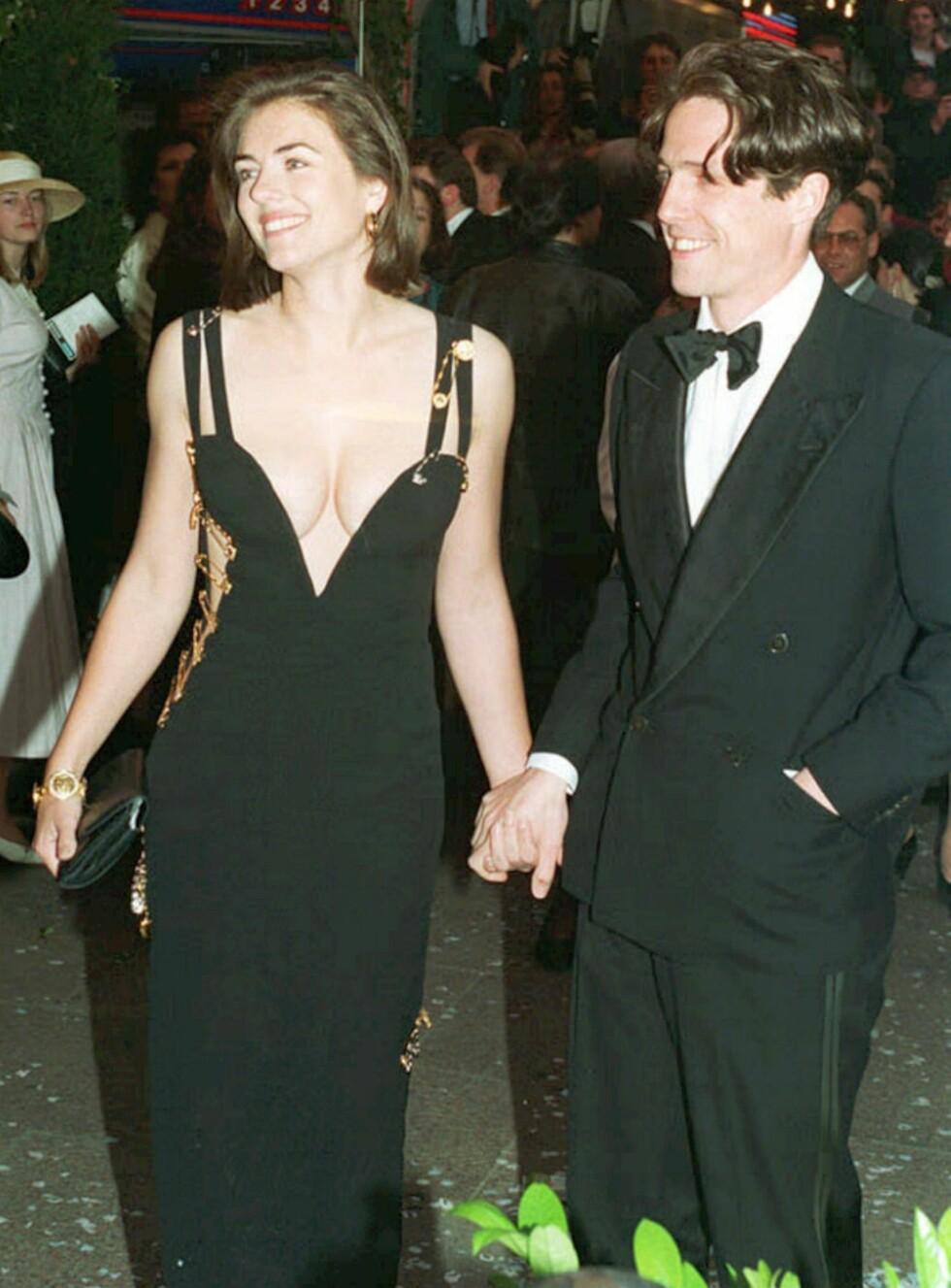 IKONISK: Elizabeth Hurley ble for alvor kjent da hun dukket opp på den røde løperen i denne Versace-kjolen i 1994, ved siden av sin ikke helt ukjente kjæreste Hugh Grant. Foto: NTB Scanpix/AP photo