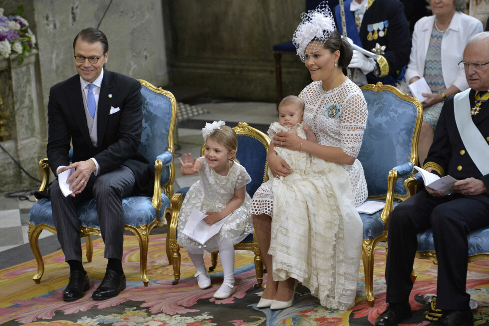 SJARMØR: Lille prinsesse Estelle hadde fått sin egen prinsessestol under dåpen i Slottskyrkan, og benyttet anledningen til å vinke til sin kjære kusine prinsesse Leonore som satt på andre siden av dåpsfonten. Foto: NTB Scanpix