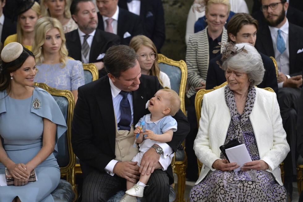 SMØRBLID: Prins Nicolas (som fyller ett år 15. juni) var lys våken under seremonien, og satt på pappas fang, side om side med tante prinsesse Sofia og prinsesse Margaretha (kongens søster).  Foto: NTB Scanpix