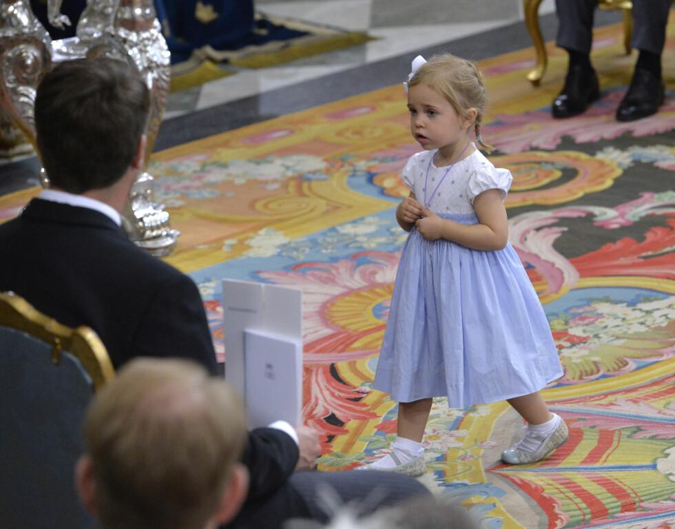 SKJØNN I BLÅTT: Prinsesse Leonore (2) var ikledd en søt, babyblå kjole og hvit sløyfe i håret. Det var tydelig at hun synes dåpsseremonien var interessant, og benyttet anledningen til å utforske området rundt døpefonten. Foto: NTB Scanpix