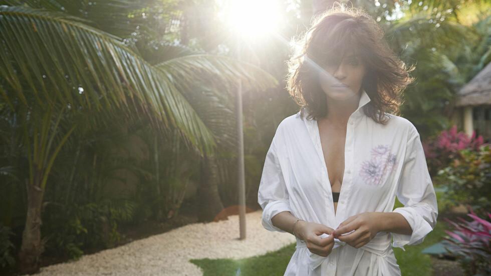 SOMMERKLÆR: Ofte er det ikke mer enn en lekker, hvit skjorte som skal til. Supermodell Helena Christensen har funnet en variant her som både har knyting og detaljer oventil. Vi elsker det! Sjekk ut flere lekre plagg i bildekarusellen nederst i saken. Foto: Splash News