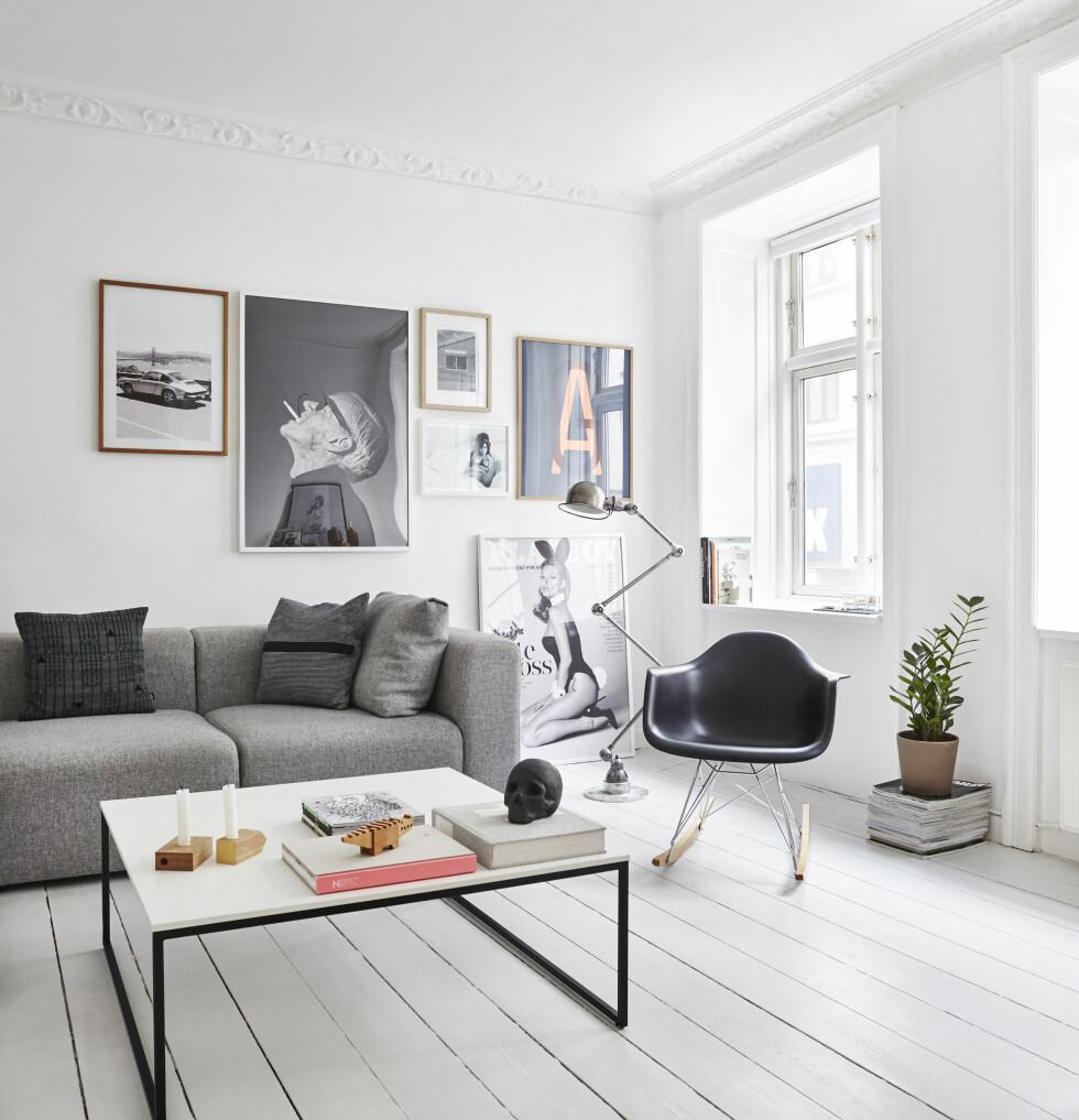 GRÅ STUE: Det lysegrå, malte gulvet får møblene til å stå tydelig frem, for eksempel Eames-stolen, sofaen fra Hay og bordet fra BoConcept. En stabel magasiner er brukt som oppsats til en plante. Lysestakene er fra DANSK Made for Rooms, og det sorte kraniet fra Normann Copenhagen.  Foto: Klix Kommunikation