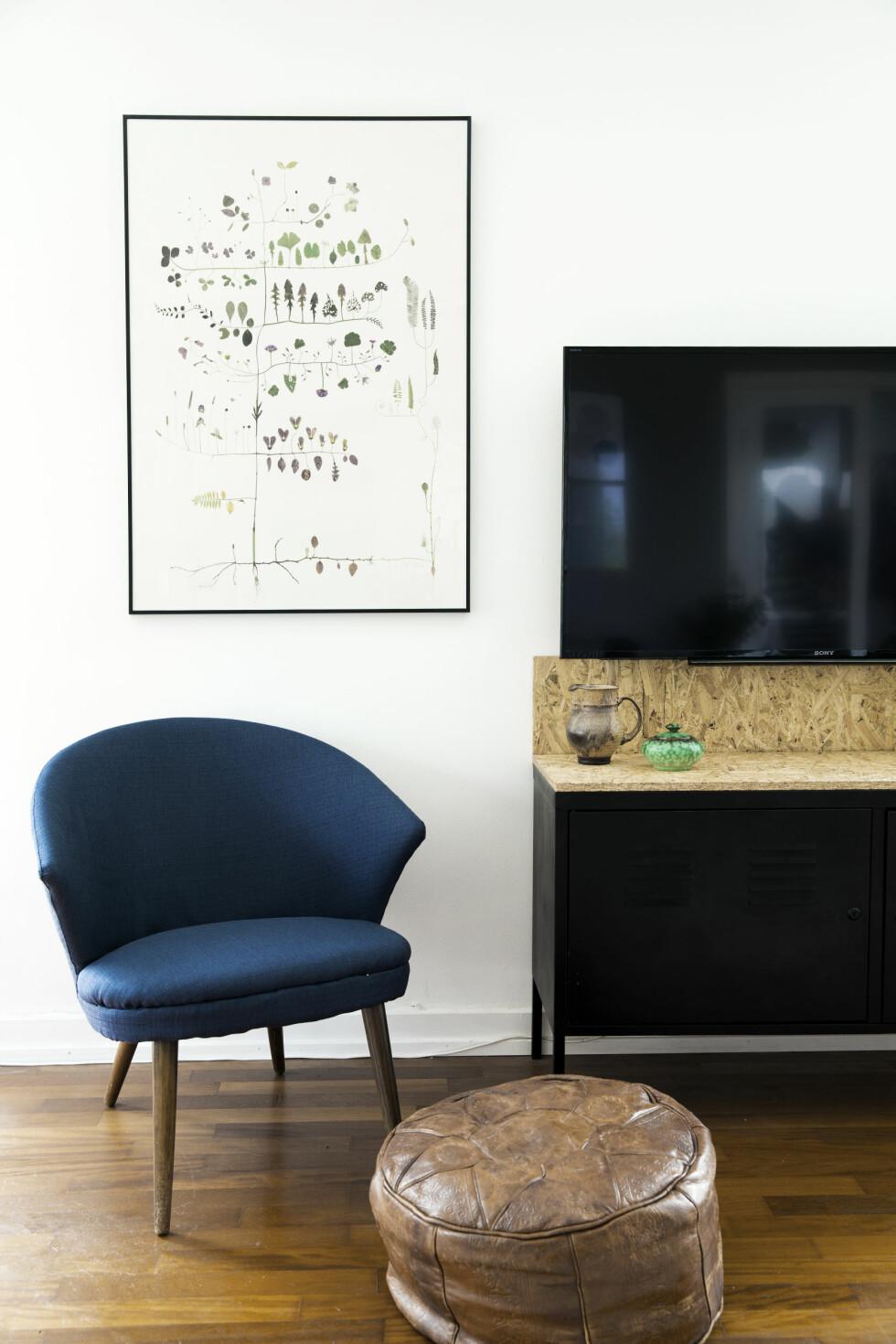 HJEMMESNEKRET: Charlotte og Filip har laget tv-benken av et Ikea-skap, som de har spraylakkert svart og lagt en sponplate på. En plate er festet slik at den går et stykke opp på veggen også, og på den måten skjules ledninger som er frest inn iveggen. Charlotte har selv trukket om stolen hun har kjøpt på auksjon. Bildet er av Lotta Olsson. Foto: Tia Borgsmidt