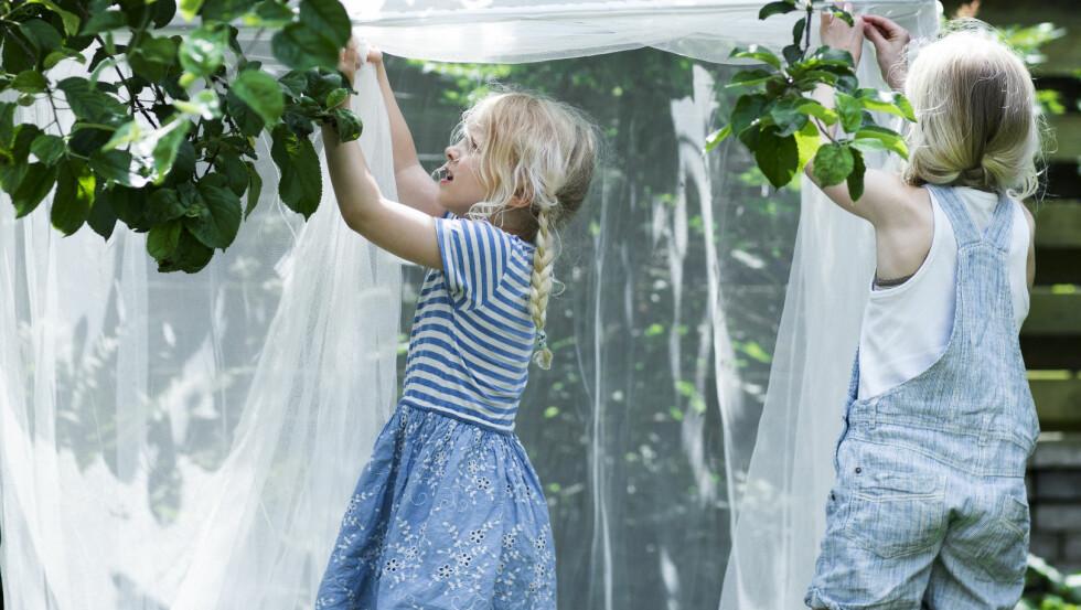 LEKESTEDER: Jentene leker seg iskyggen av et frukttre med et svalt nettingtelt fra Ikea.   Foto: Tia Borgsmidt