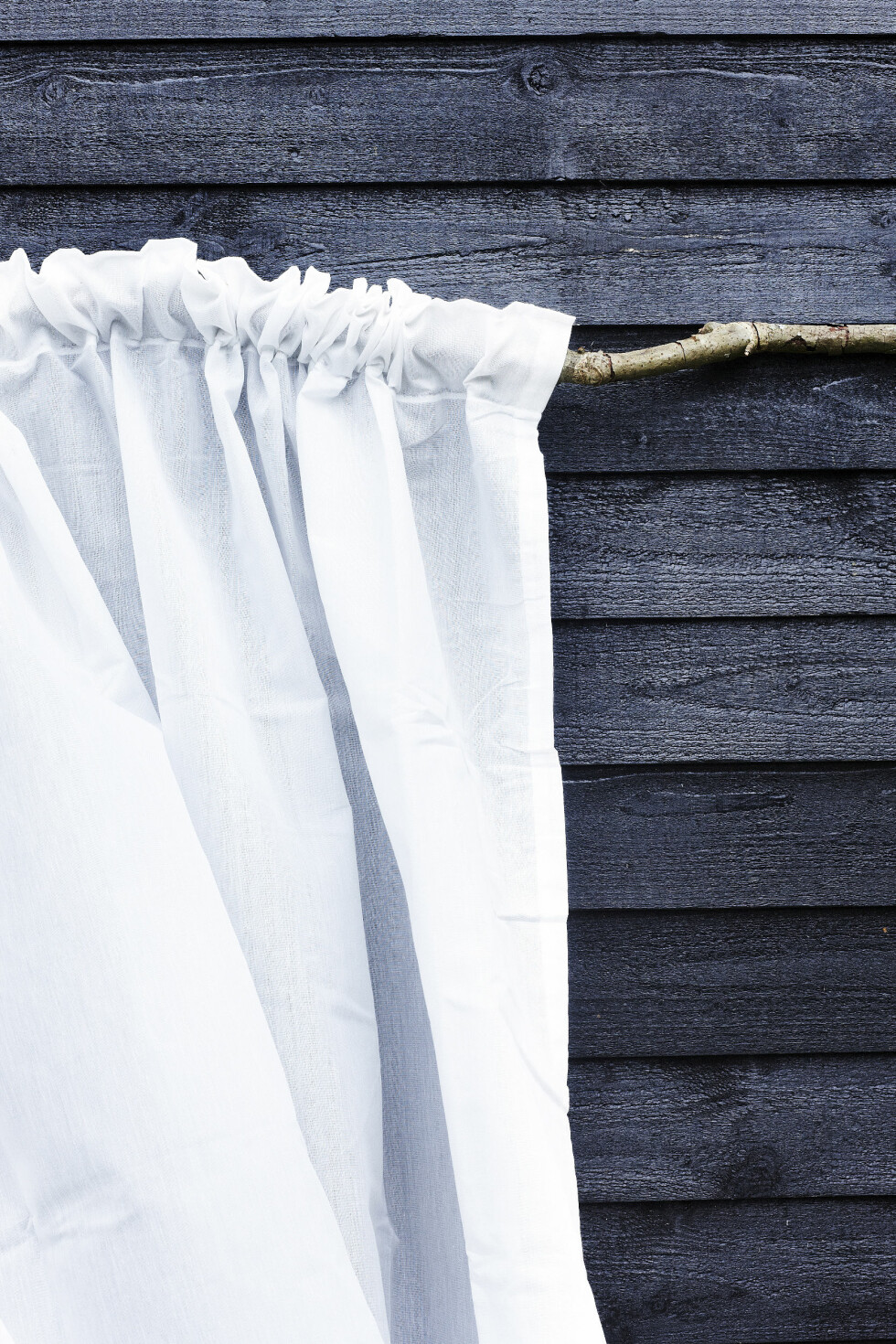 VEGG I VINDEN: Tekstiler er enkel måte å skape en hyggelig stemning på. Tenk gjerne puter, pledd og gulvtepper – men gardiner er også effektfullt. Du kan for eksempel henge opp en gardin på en lang pinne med snor i begge ender, og bruk det som en romdeler på terrassen.  Foto: Mette Wotkjær