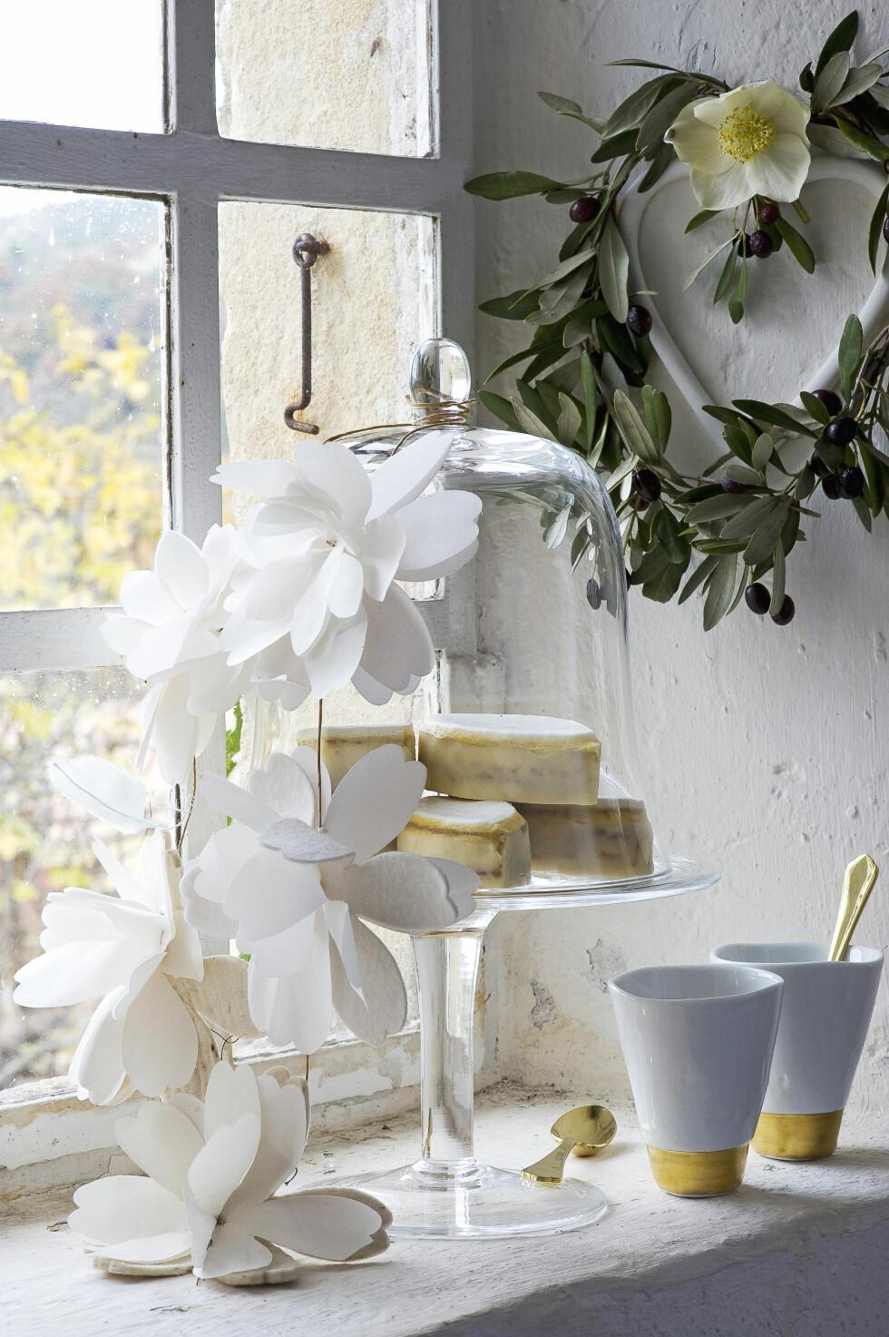 EVIGVARENDE BLOMSTER: Legg flere tynne ark oppå hverandre, brett en gang og fest dem sammen med et par stifter i bretten. Klipp deretter ut en halv blomst, som blir hel når du bretter ut arket. Tre blomstene etter hverandre på en tynn ståltråd, hjelp til med litt lim. PS! Du får også  kjøpt fine blomstergirlander på blant annet etsy.com. Foto: Scanpix