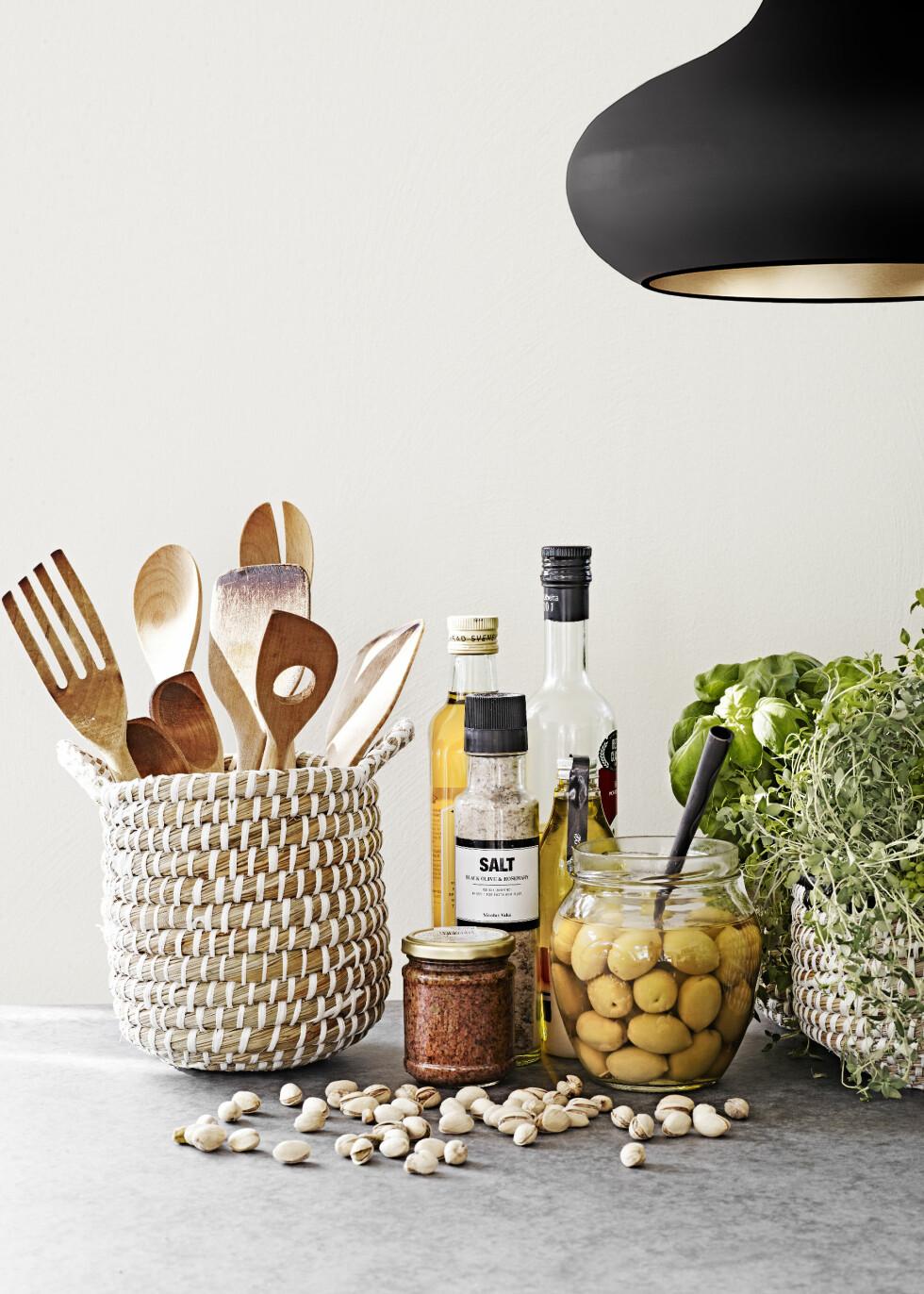 FOR ALLE SANSER: Slipp sommeren til i kjøkkenets vinduskarm og på benken. Litt pesto, olje og oliven til de lette salatene vi planlegger nå, fylt på fine flasker og krukker, gir deilig middelhavsstemning. Ekstra fint blir det med sommerlige kurver til urter og redskaper. Tips! Urter fra hagesentrene holder seg lenger enn urter fra daglivarebutikken. Dette fordi de er beregnet på dyrking i motsetning til å spises umiddelbart. Foto: Sara Svenningrud