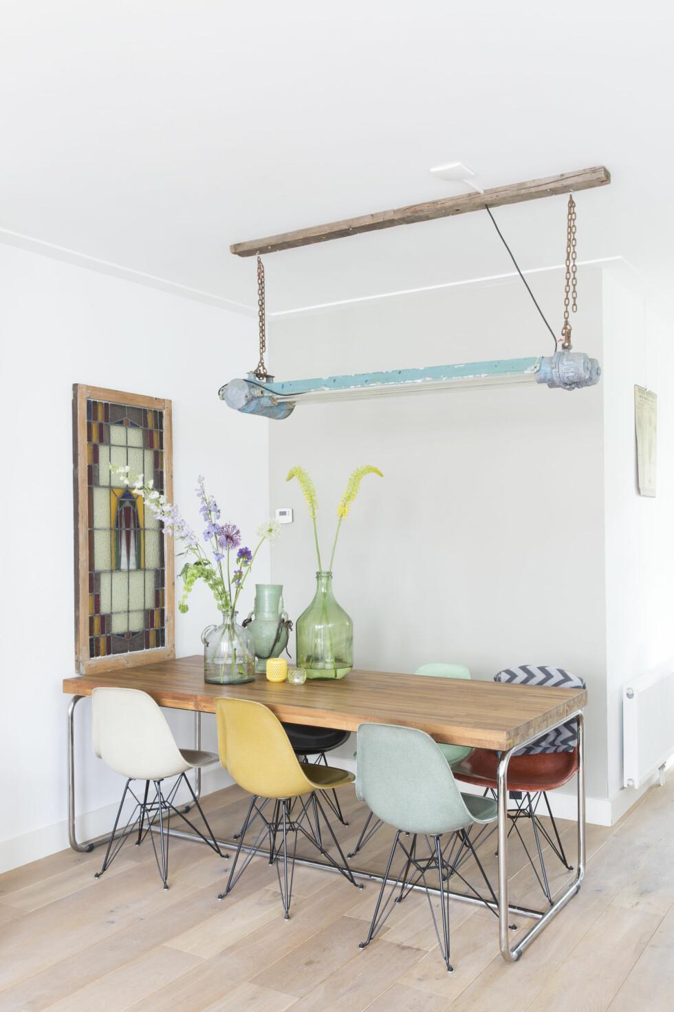 TRENDY SPISESTUE: Glassmaleriet på veggen reddet Rick fra en gammel kino for 19 år siden. Eames-stolene er vintage fra modernvintage.nl og bordet fra Loods5.nl.   Foto: Margriet Hoekstral