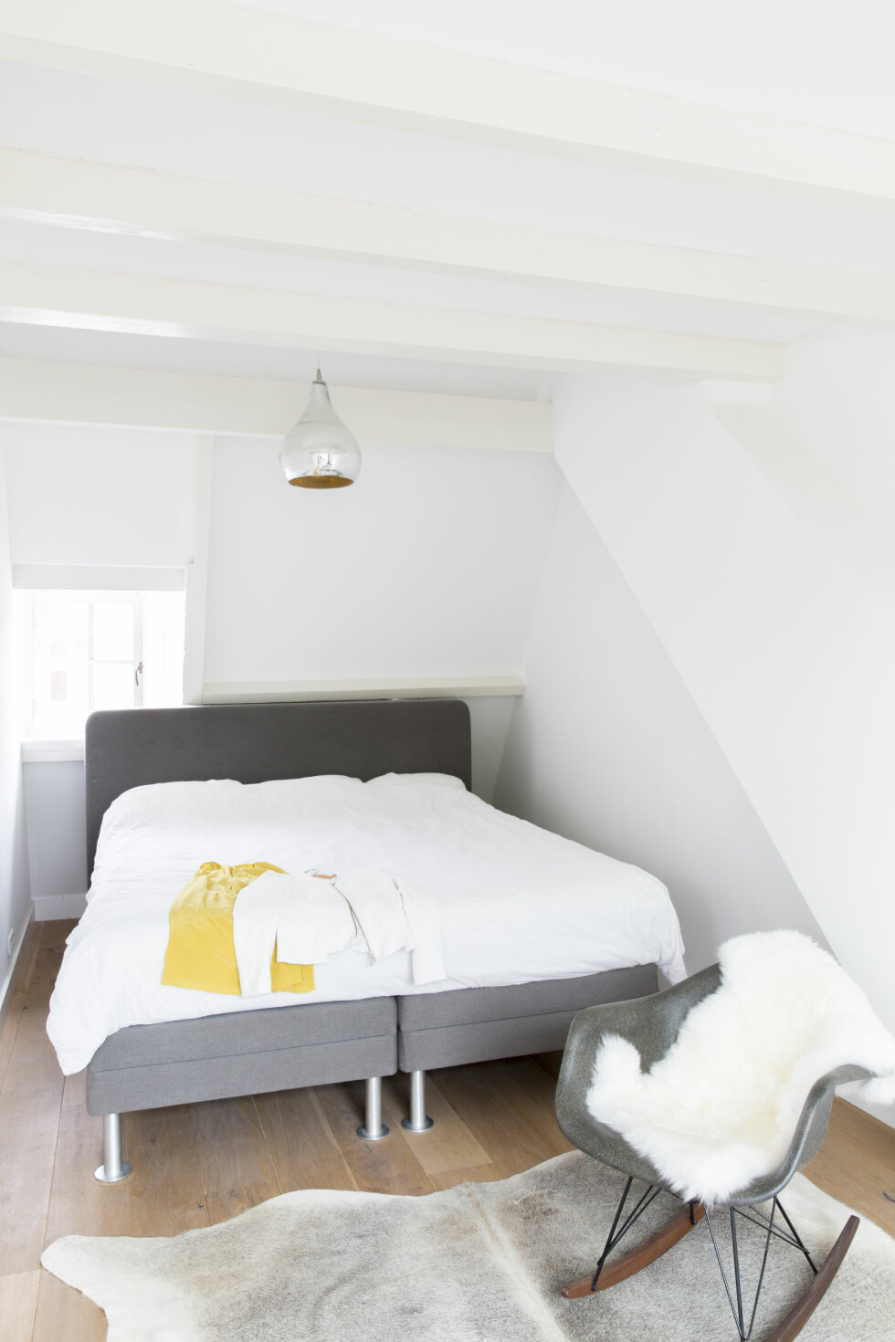TRENDY SOVEROM: Det lille, enkle soverommet ligger iden øverste etasjen med utgang til takterrassen, og her er paletten holdt helt rolig og delikat i hvitt og grått. Gyngestolen er vintage fra modernvintage.nl. Linsengetøy er supertrendy, og det er ikke rart: Råfint å se på – og en drøm å sove i! Foto: Margriet Hoekstral