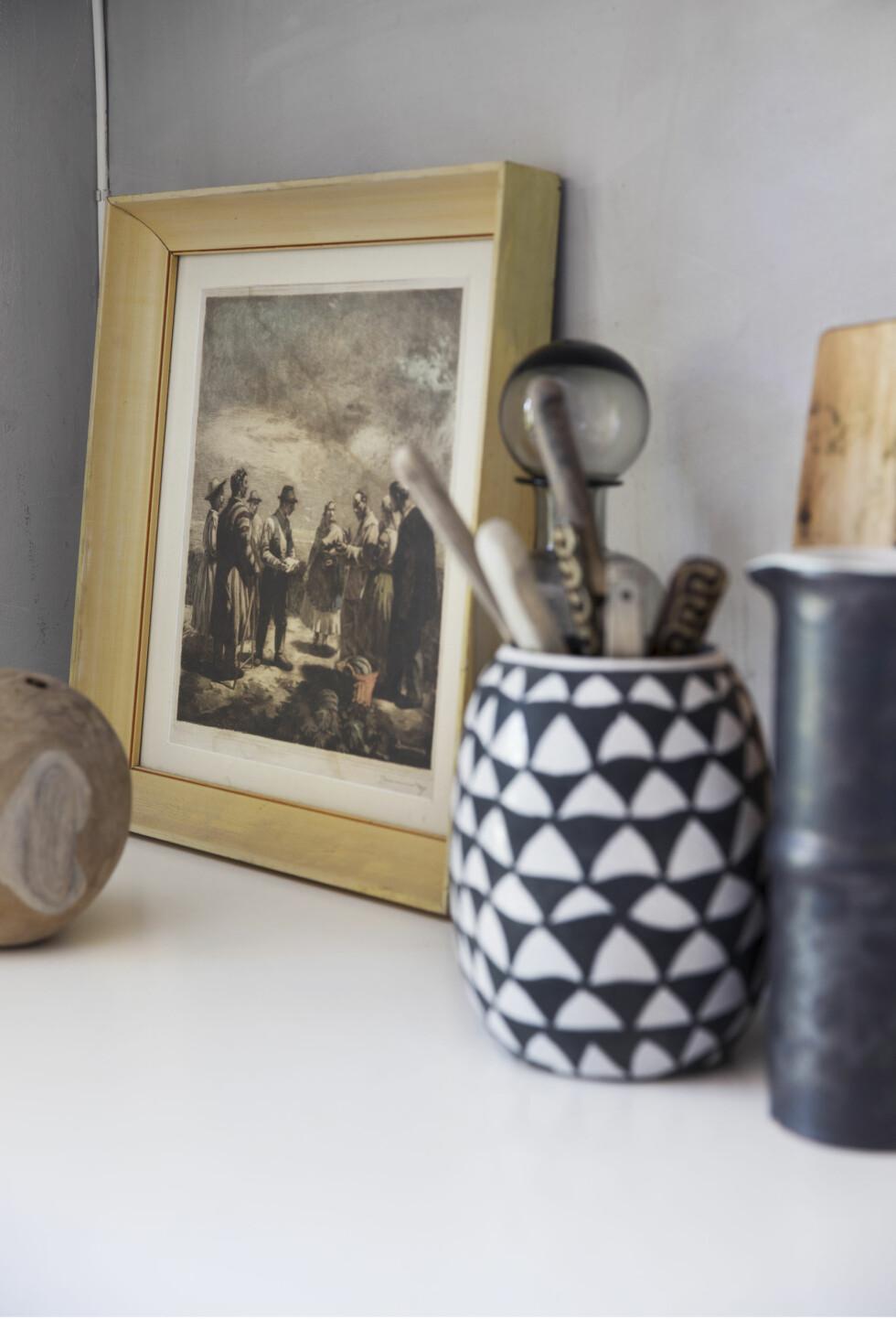 KUNST PÅ KJØKKENET: Også på kjøkkenbenken har kunsten en plass. Det vakre, gamle bildet er kjøpt på et marked i Ungarn. Vasen fra Eske brukes til kjøkkenredskaper.   Foto: Yvonne Wilhelmsen