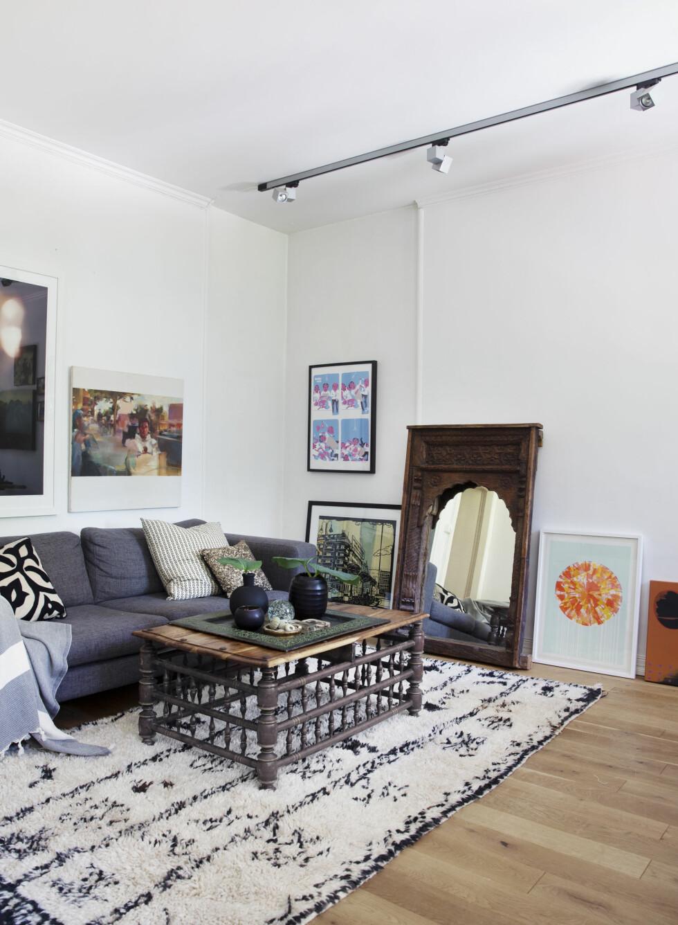 BILDER PÅ GULVET: De to bildene nærmest sofaen er av den ungarske kunstneren Szolt Vidák, som har stilt ut i galleriet til Eva Christin. Sofaen er fra Raun og kjøpt brukt. Bordet er arvegods og fra Bali. Alle bildene trenger ikke henges opp. Det kan bli flott å stille dem på gulvet også!  Foto: Yvonne Wilhelmsen