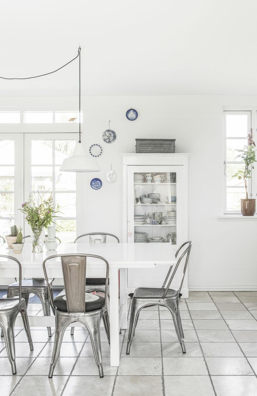 HJEMMELAGD BORD: Annette har laget sitt eget plankelangbord ved å male, lakkere og feste planker på et Ikea-bord. De dekorative tallerknene på veggen er dels loppefunn, dels arvede. Spisestolene er Tolix-stoler. Trekassen i hjørnet er fra butikken ReUse i Aalborg, og lampen er fra Hay. Vitrineskapet er funnet på Den Blå Avis. Foto: Frederikke Heiberg