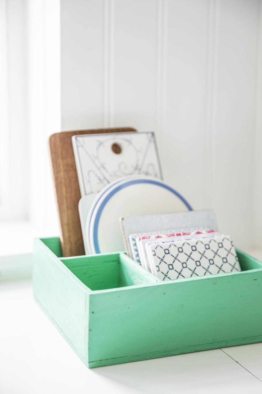 FLISER TIL PYNT: På kjøkkenbordet står en gammel trekasse med forskjellige fliser fra Sinnerup, de brukes både som gryteunderlag og pynt. Foto: Frederikke Heiberg