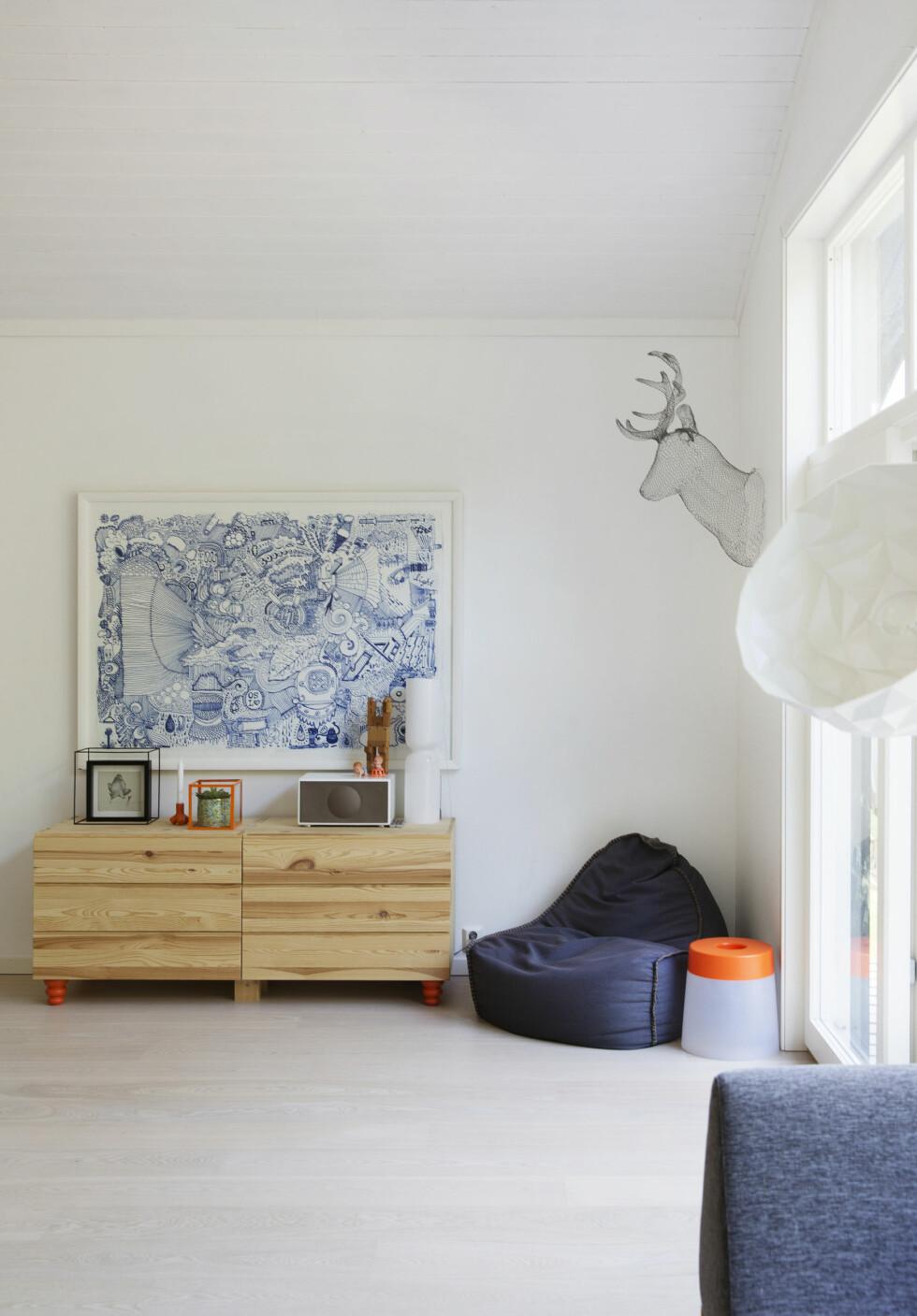 SPESIELT MALERI: Maleriet på veggen er egentlig en kulepenntegning på en bitteliten lapp som er blåst opp. — Det er ment som en kjærlighetserklæring til Oslo, og ble fullført etter 22.juli, forteller Siri. Kunstneren heter Mattis Bentzen. Hjortehode i hønsenetting fra Escobar, skapene er Ikeas billigste; Ivar med nye bein fra Prettypegs. Det oransje ved siden av stolen er en oppladbar lampe fra Ikea. Foto: Yvonne Wilhelmsen