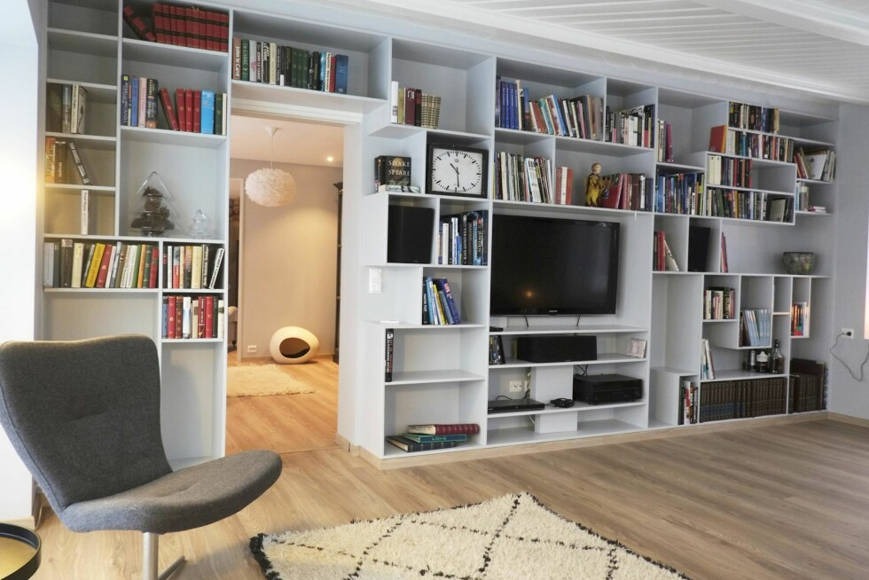 BIBLIOTEKET: Dette rommet var fullt av bøker før oppussingen også, men nå er det langt mer moderne. En spesialsnekret, gråmalt bokhylle rommer det meste. Den grå stolen er fra Living. Foto: Hege Landrø Johnsen