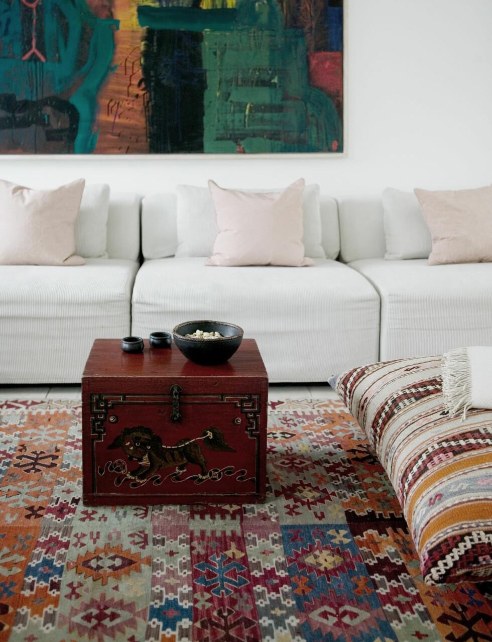 DELIKAT MIKS: Det store oljemaleriet er av Jens Birkemose. Den store sofaen inviterer til kos for hele familien.Eksotisk kelim mot sart pudderrosa gir en delikat og dempet miks.   Foto: Kira Brandt/House of Pictures