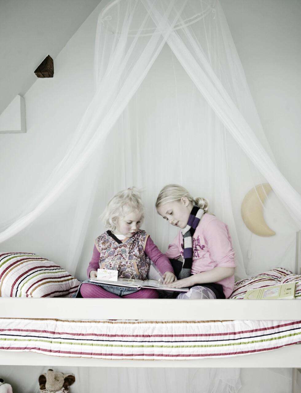 SØSKENKJÆRLIGHET: Ida leser for lillesøster Ingrid. Sengeteppe og puter fra Ikea. Foto: Kira Brandt/House of Pictures