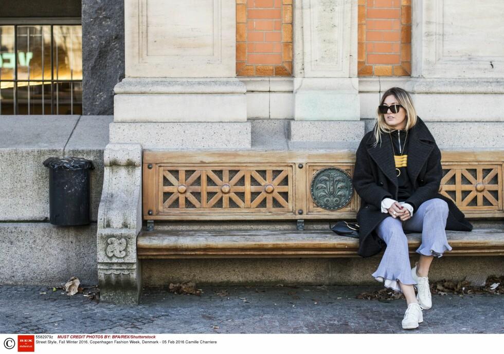 <strong>BUKSER MED DETALJERT KANT:</strong> Camille Charriere tar en pust i bakken under moteuken i København. Disse buksene tilfører antrekket et interessant element - vi liker! Foto: Rex Features
