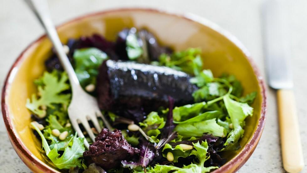 TRADISJONELL RETT: Blodpudding trenger ikke være kjedelig. Det fins mange spennende og smakfulle tips som kan friste oss til å få i oss denne næringsrike puddingen. Her servert med en lekker grønn salat og pinjekjerner.  Foto: StockFood