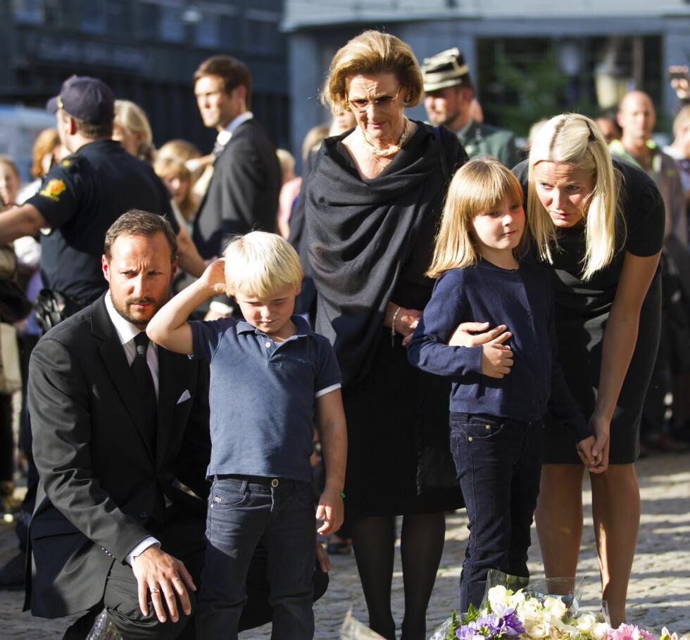 TO TIÅR SENERE: I 2011 hadde kongeparet sittet på tronen i 20 år, og vi fikk erfare at deres rolle ble viktigere enn noen gang tidligere. Hele kongefamilien tok aktivt del i sorgarbeidet etter terroren som rammet oss 22. juli. Her ser dronning Sonja og svigerdatter Mette-Marit, sønnen kronprins Haakon og barnebarna prins Sverre Magnus og prinsesse Ingrid Alexandra på blomsterhavet utenfor Oslo Domkirke. Foto: NTB Scanpix