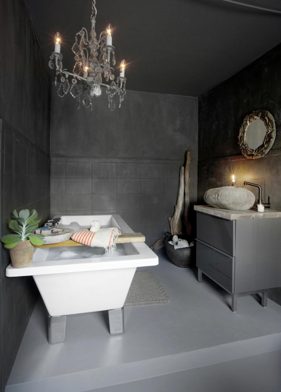 FAVORITTROMMET: Det grå gjestebadet hadde opprinnelig fire forskjellige flisetyper. — Vi flytsparklet gulvet, og malte veggene med kalkmaling fra Pure Original toppet med to strøk sealer. Tak og gulv er malt med vanlig, helmatt gråmaling. Den antikke lysekronen er fra Paris og er prikken over i-en. Speilet har Ive laget selv av drivved, vasken er fra Bali, benkeplaten er laget av Drivved.no,  badekaret sto i huset da de kjøpte det.   Foto: Nina Ruud